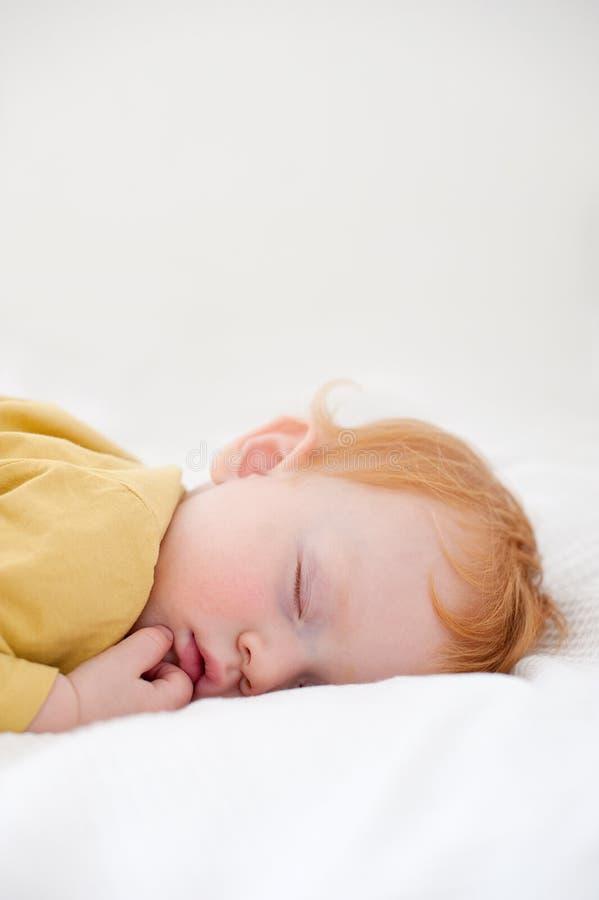 Rothaarigekind schläft auf einem weißen Blatt lizenzfreies stockfoto