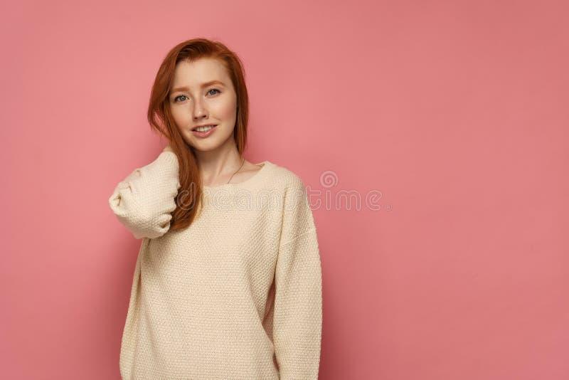 Rothaarigemädchen berührt ihr Haar und Lächeln auf rosa Hintergrund stockfotos