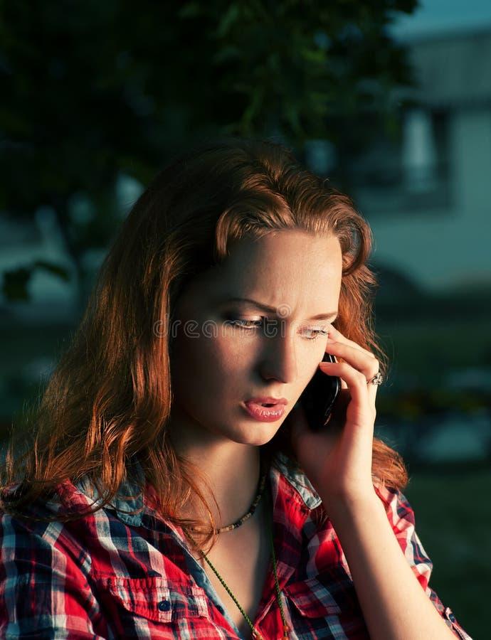 Rothaarigemädchen, das durch Handy nennt lizenzfreie stockfotos