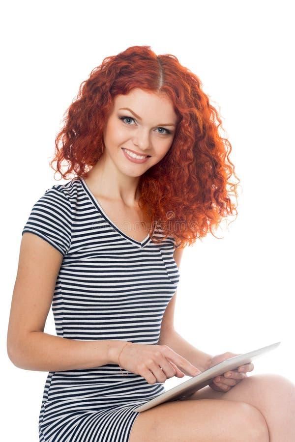 Rothaarigemädchen, das einen Tabletten-PC verwendet lizenzfreie stockbilder