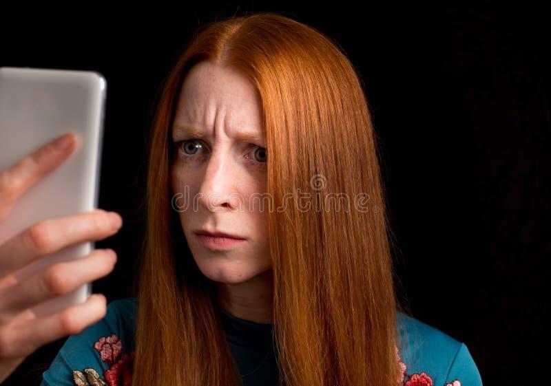 Rothaarigemädchen, das Telefon betrachtet lizenzfreies stockbild