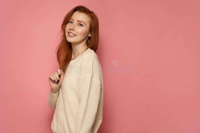 Rothaarigemädchen steht seitlich zur Kamera, berührt ihr Haar und Lächeln auf rosa Hintergrund stockfotografie