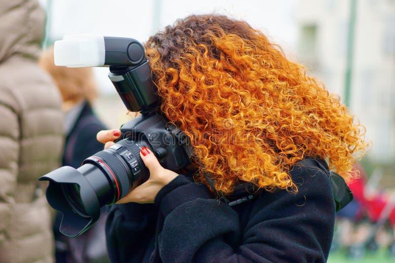 Rothaarigephotographfrau mit Berufskamera lizenzfreie stockfotografie