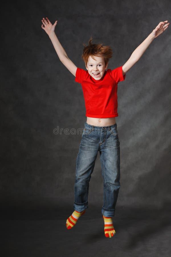 Rothaariger Junge, der auf einen dunklen Hintergrund springt Getrennt auf weißem Hintergrund stockbilder