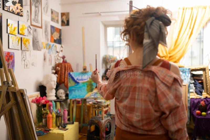 Rothaariger Künstler mit Haarbrötchenholding-Malereibürste lizenzfreie stockfotografie