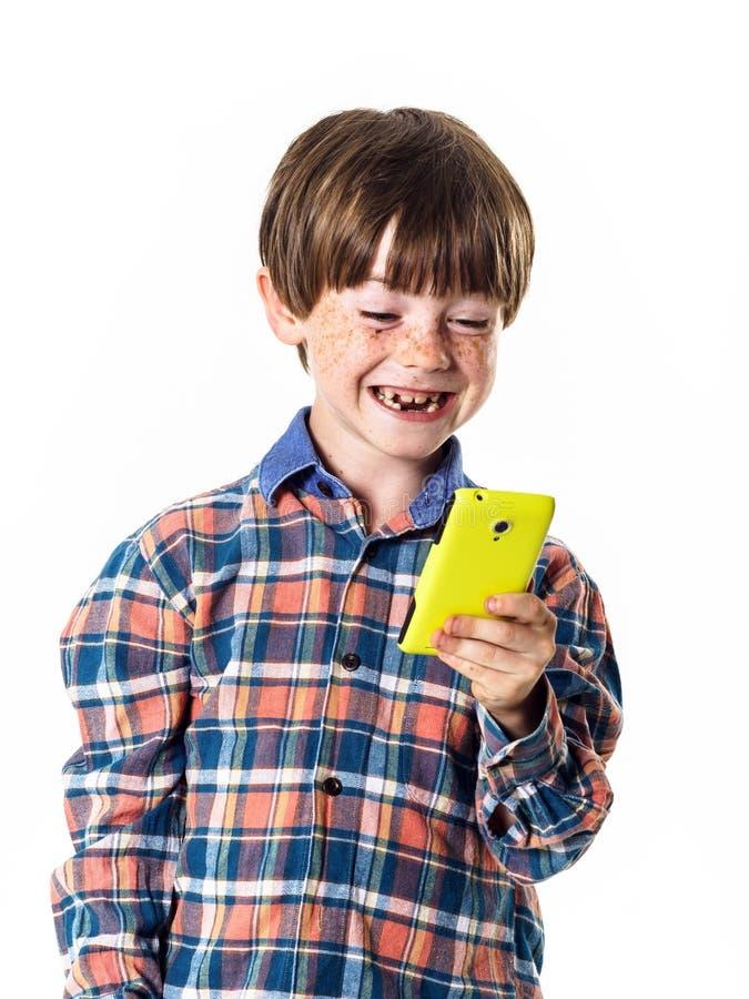 Rothaariger lustiger Junge mit Handy lizenzfreies stockfoto