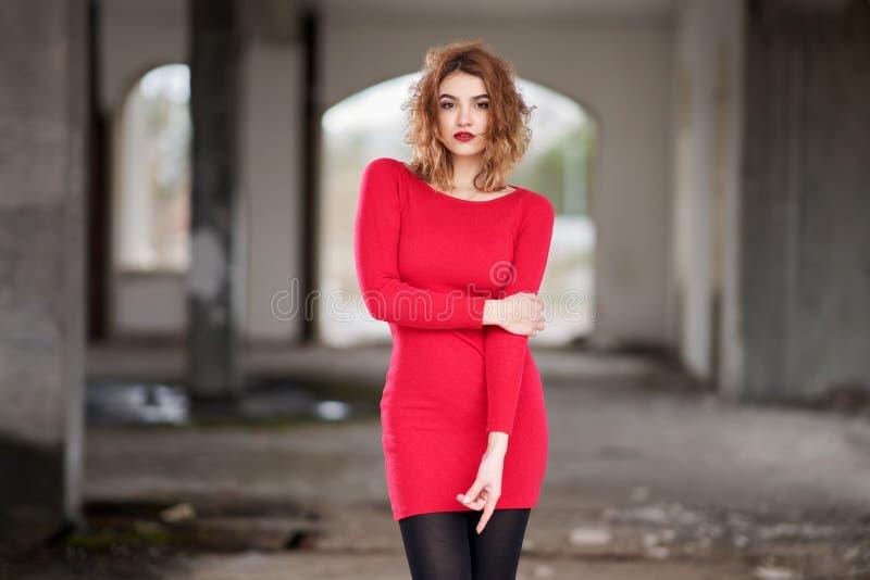 Rothaariges junges Mädchen in einem kurzen roten Kleid, das in einem verlassenen Haus aufwirft lizenzfreie stockbilder