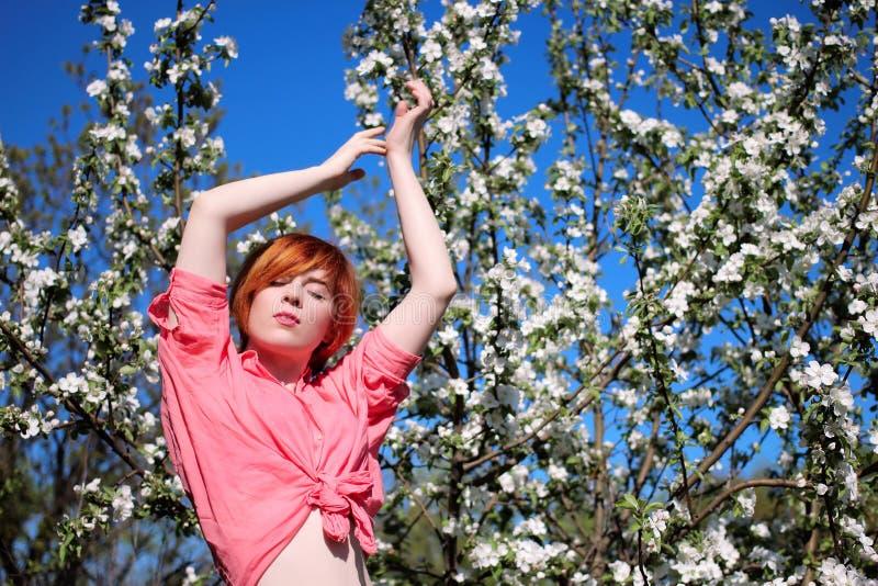 Rothaariges Mädchen auf einem Hintergrund von blühenden Bäumen, Mädchen zieht ihre Hände aufwärts, Porträt des Frühlingsmode-Mädc stockbild