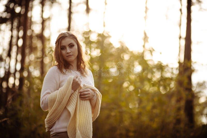 Rothaariges Mädchen in der hellen Kleidung auf einem Hintergrund des Herbstwaldes stockfotografie