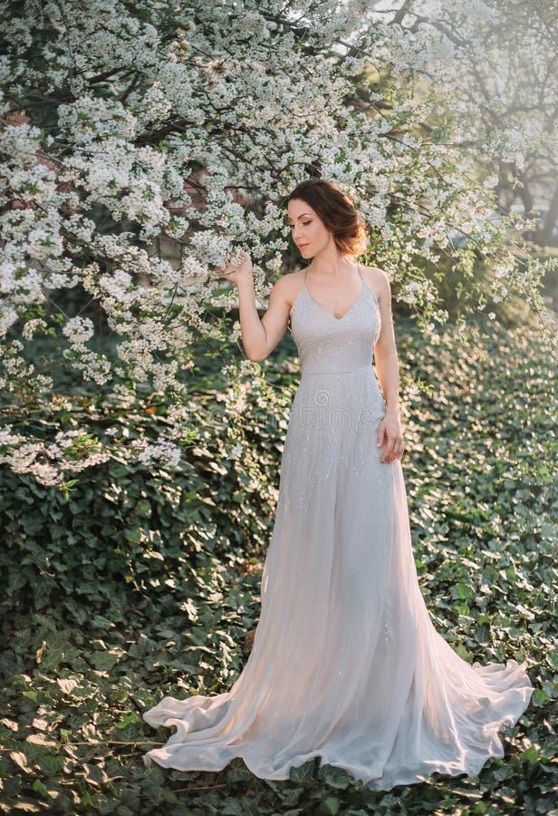 Rothaariges Mädchen in einem bescheidenen, sehr langen, grauen Kleid in der rustikalen Art Porträt der Braut vor dem hintergrund  stockbild