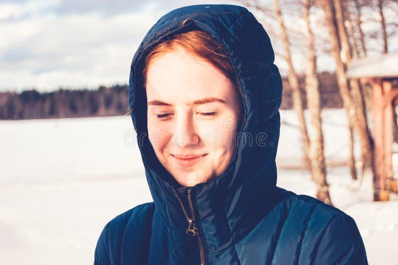 Rothaariges Mädchen freut sich in den ersten Strahlen der Frühlingssonne stockbild