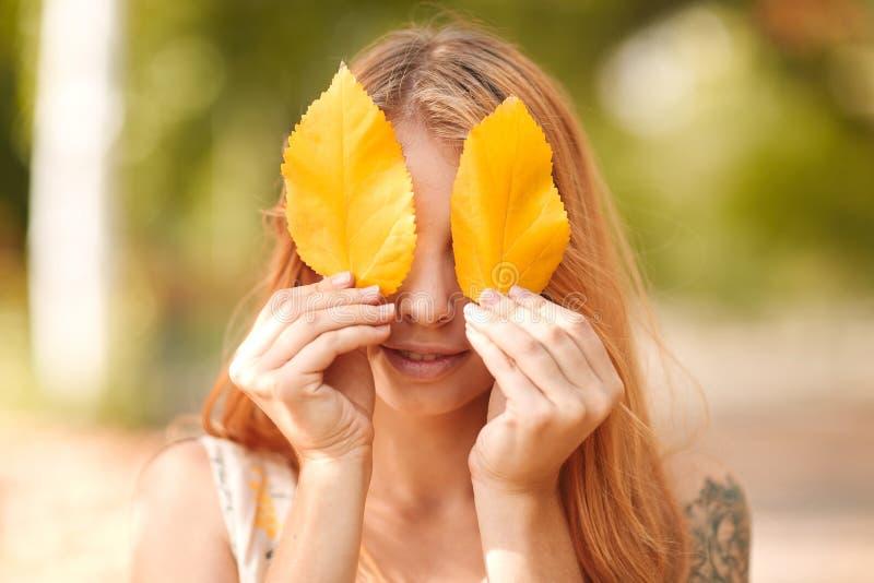 Rothaariges Mädchen schließt ihre Augen mit Herbstlaub stockbild