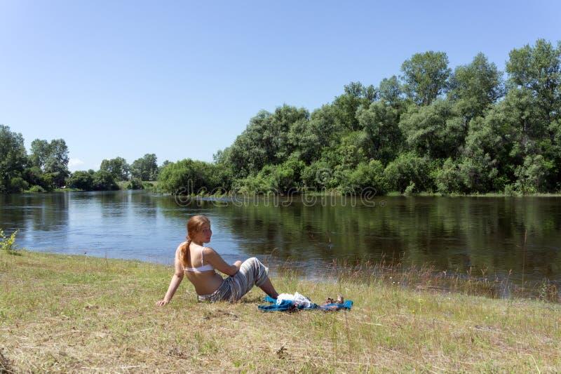 Rothaariges Mädchen sitzt auf der Bank des Flusses gegen einen Hintergrund von Bäumen, an einem sonnigen Tag des Sommers stockfotos