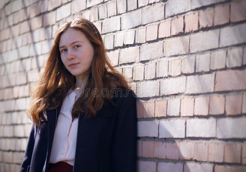 Rothaariges Mädchen steht nahe einer Backsteinmauer stockfotografie