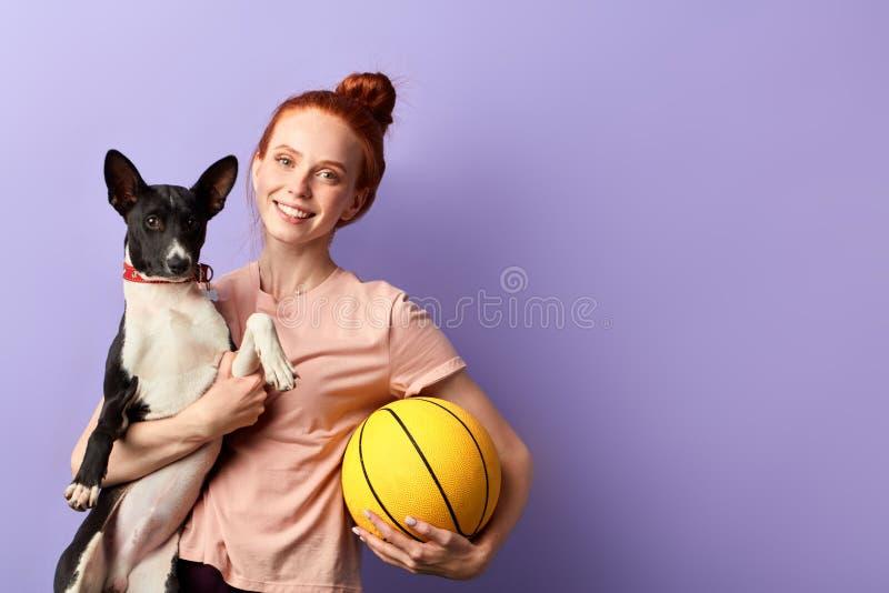 Rothaariges schönes Mädchen, das einen Ball und ein Haustier hält und zur Kamera aufwirft stockfotografie