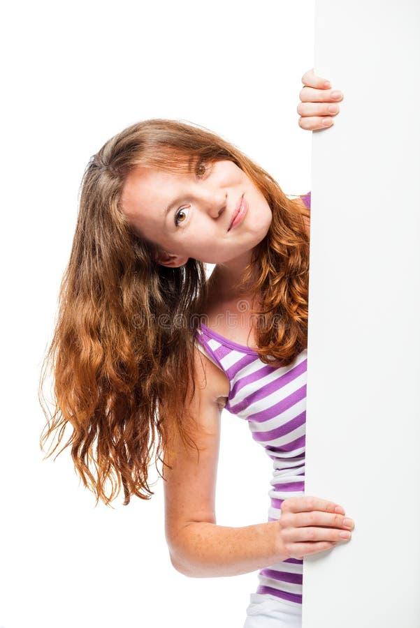 Rothaariges schönes Mädchen, das heraus von hinten das Plakat späht stockfotos