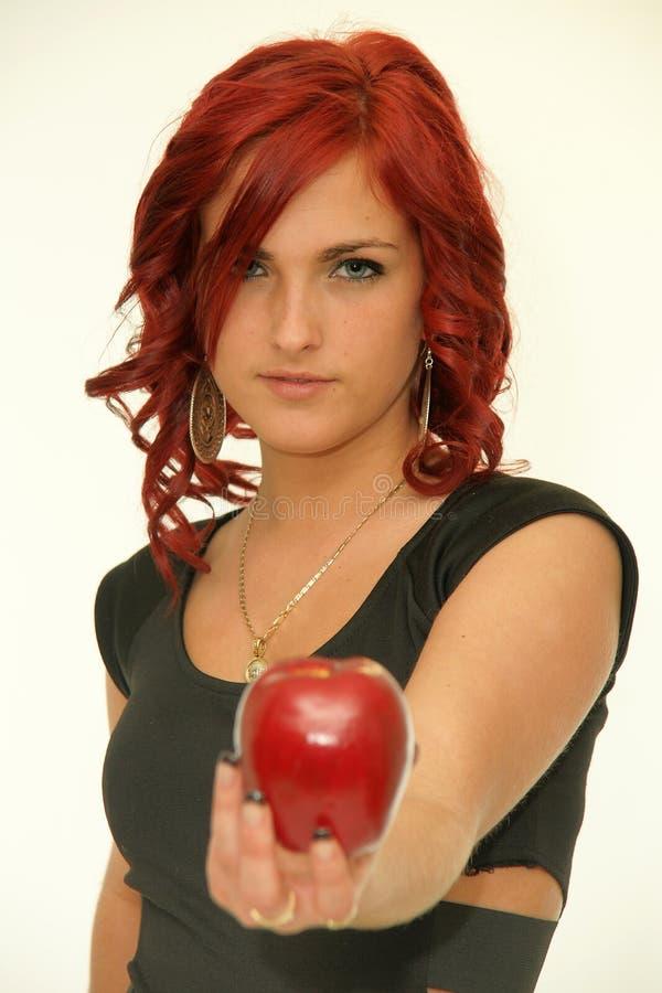 Rothaarigeschönheit mit rotem Apfel stockfotos