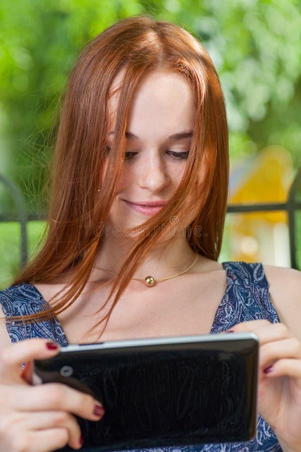 Rothaarigestudent, der an einem Baum unter Verwendung ihrer Tablette auf Collegecampus sich lehnt lizenzfreie stockfotografie