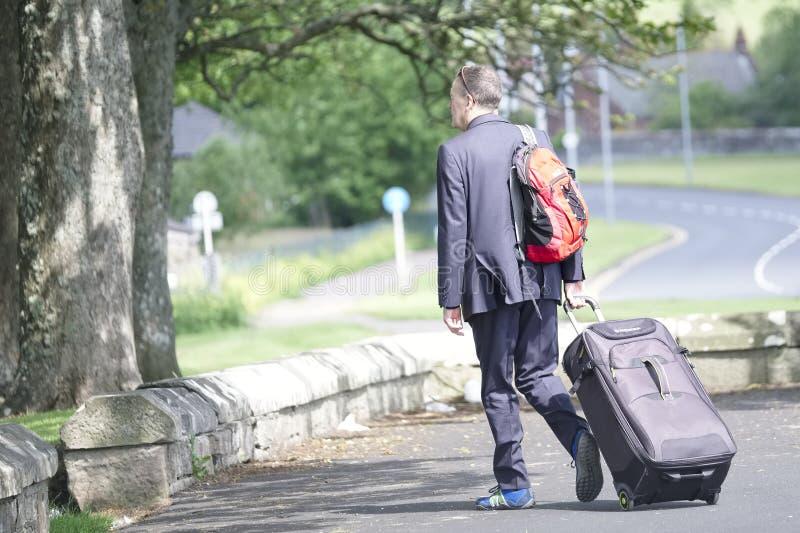 Rothesay, Eiland van Bute/Schotland - 21 Juni 2019: Mannelijke toeristenreiziger die met koffer op wielen weg kruisen royalty-vrije stock afbeelding