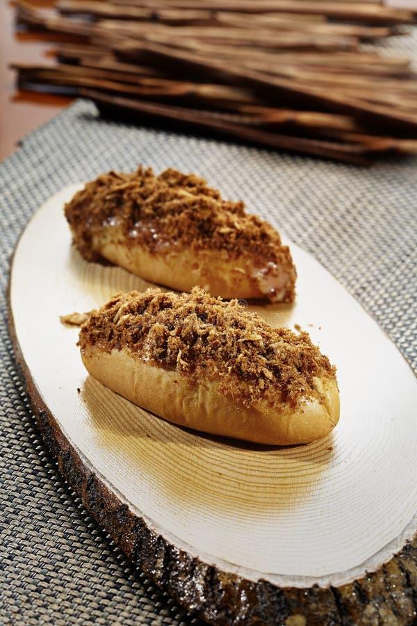 Roti Abon Il pane tagliuzzato della carne è disposto su un piatto di legno fibroso con il fondo della cannella immagine stock