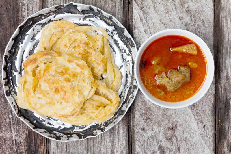 Roti canai with spicy curry. On old wood, Top View royalty free stock photos