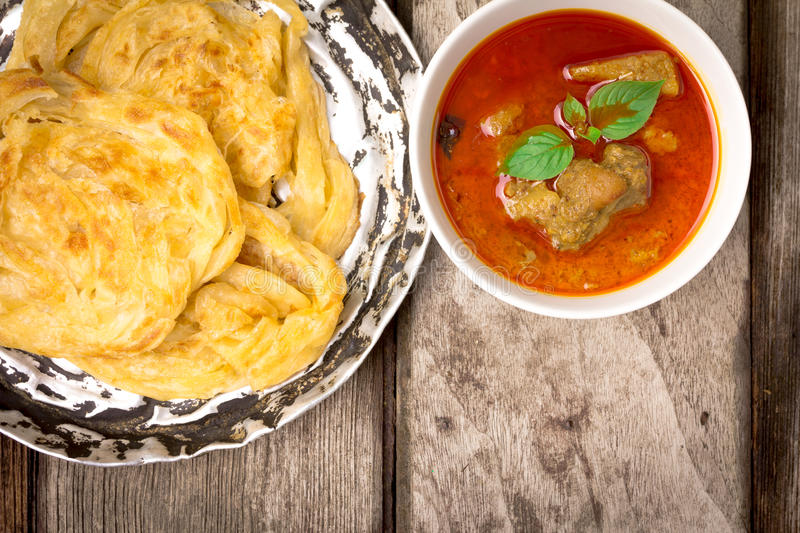 Roti canai with spicy curry. On old wood, Top view stock images