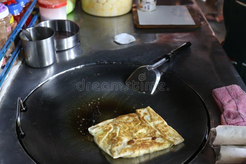 Roti eggs la parola tailandese fritta in una via del mercato di notte, alimento indiano, flatbread della focaccia, canai di roti, fotografie stock