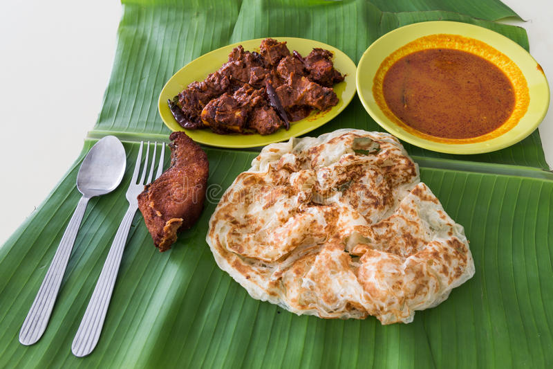 Roti prata on banana leaf with masala mutton, fish, curry stock photography