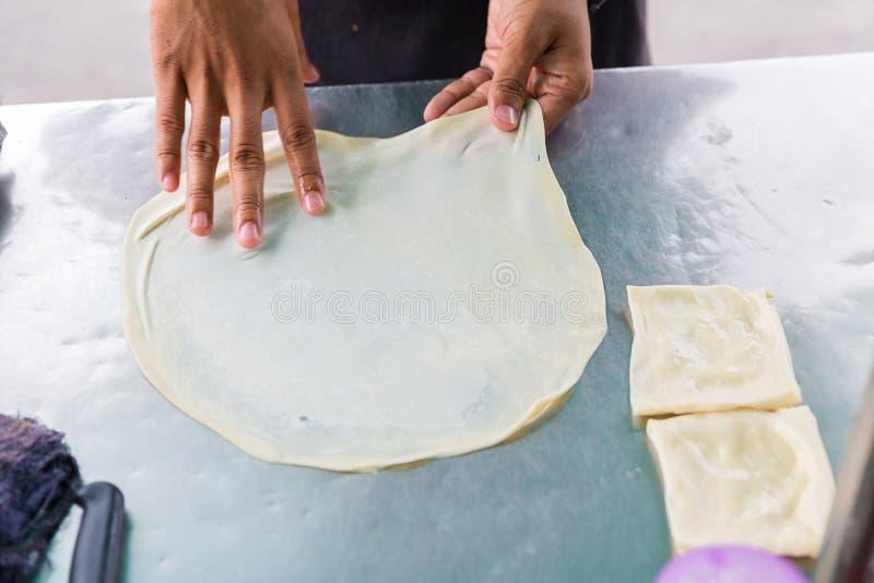 Roti que hace, roti trilla la harina por el fabricante del roti con aceite Comida tradicional india de la calle Plátano y huevo t imágenes de archivo libres de regalías