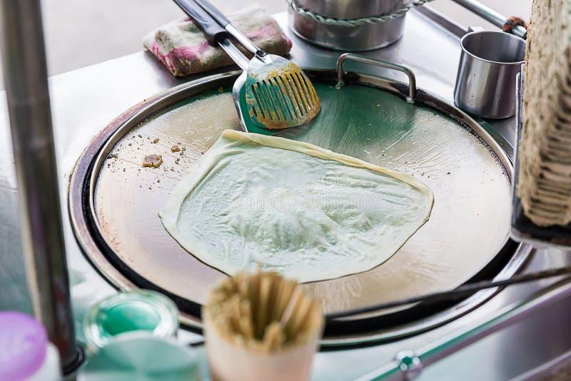Roti que hace, roti trilla la harina por el fabricante del roti con aceite Comida tradicional india de la calle Plátano y huevo t fotos de archivo