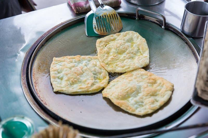 Roti que hace, roti trilla la harina por el fabricante del roti con aceite Comida tradicional india de la calle Plátano y huevo t fotografía de archivo