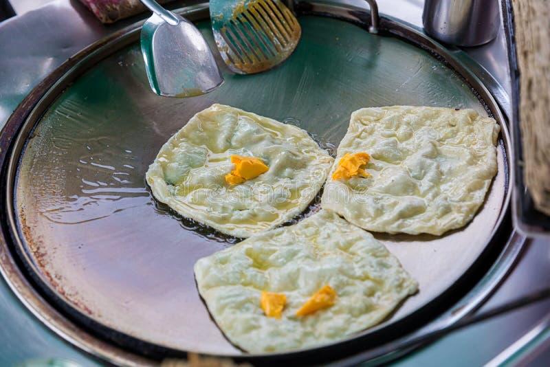 Roti que hace, roti trilla la harina por el fabricante del roti con aceite Comida tradicional india de la calle Plátano y huevo t fotos de archivo libres de regalías