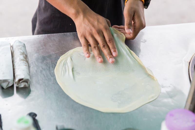 Roti que hace, roti trilla la harina por el fabricante del roti con aceite Comida tradicional india de la calle Plátano y huevo t imagen de archivo
