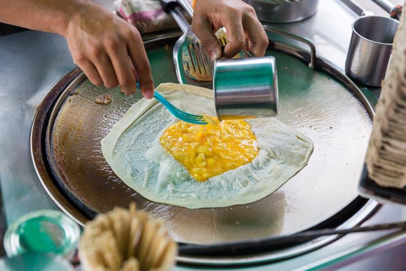 Roti que hace, roti trilla la harina por el fabricante del roti con aceite Comida tradicional india de la calle Plátano y huevo t fotografía de archivo libre de regalías