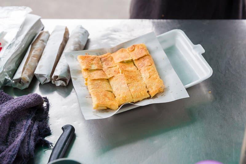 Roti que hace, roti trilla la harina por el fabricante del roti con aceite Comida tradicional india de la calle Plátano y huevo t imagenes de archivo