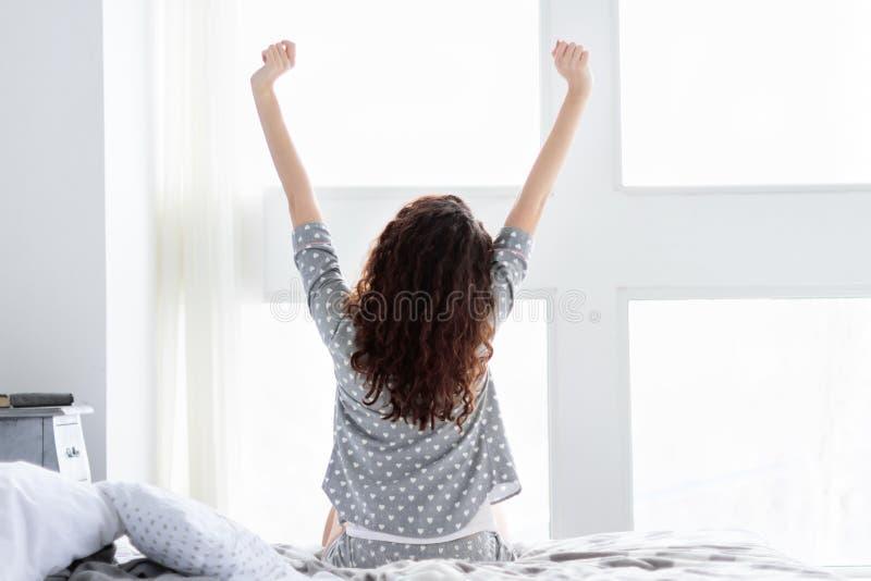 Rotina diária Fêmea nova com o cabelo encaracolado fraco acima na manhã foto de stock royalty free