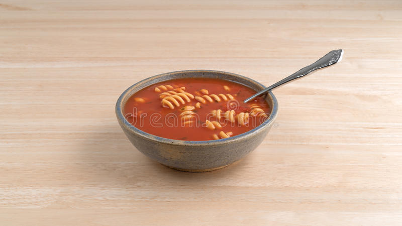 Rotini tomato soup in bowl with spoon on table stock image