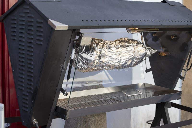 Rotisserie móvil con el escupitajo del cerdo fotografía de archivo