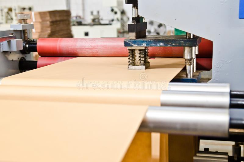 Doypack making packaging machine in modern factory with brown kraft paper rolls and plastic film running royalty free stock image