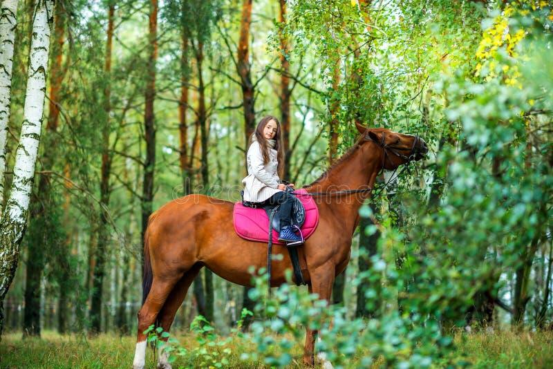 Rotolamento dell'adolescente della ragazza sul suo cavallo favorito in un bello parco fotografia stock