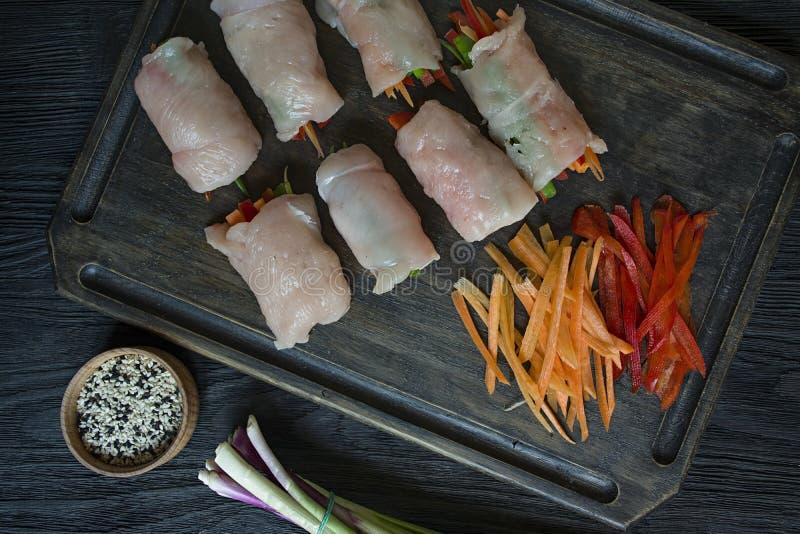 Rotoli casalinghi con il petto di pollo fresco con i verdi, fette della carota, peperone dolce su un tagliere scuro Il concetto d immagini stock libere da diritti