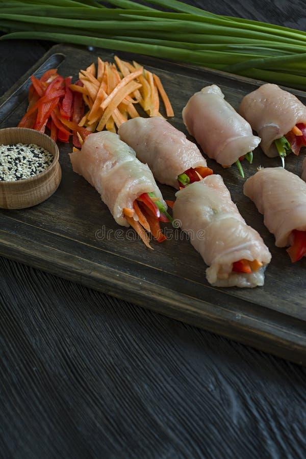 Rotoli casalinghi con il petto di pollo fresco con i verdi, fette della carota, peperone dolce su un tagliere scuro Il concetto d immagine stock