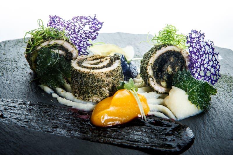 Rotoli decorati moderni del pesce del primo piano farciti con le erbe fotografie stock