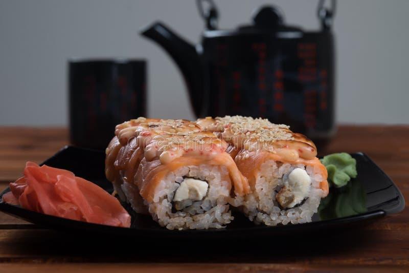 Rotoli del rotolo, di California di sushi di Filadelfia con lo zenzero e wasabi sulla banda nera immagini stock libere da diritti