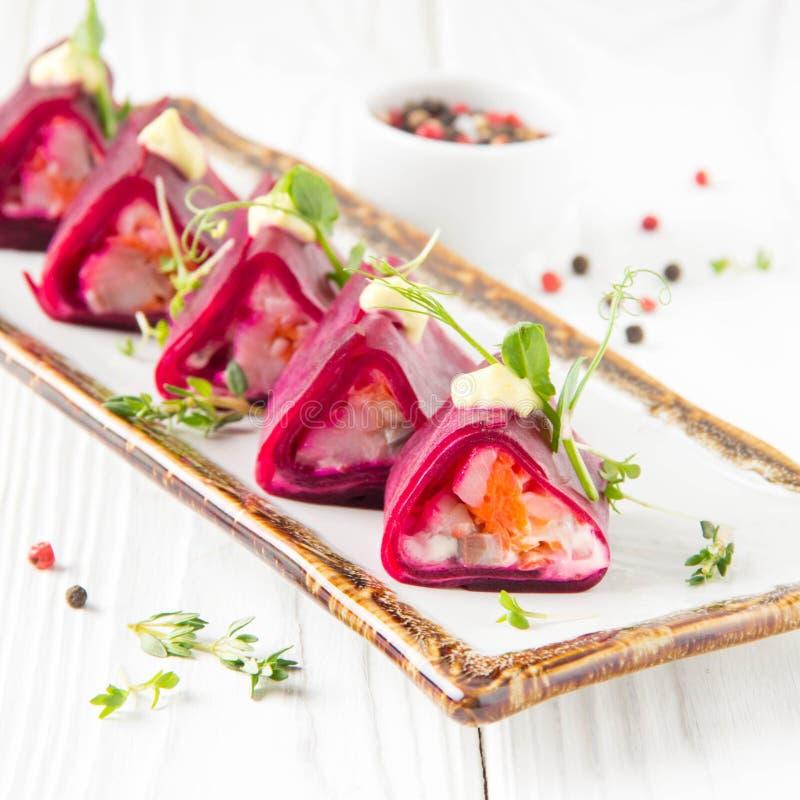 Rotoli della barbabietola farciti con le verdure e l'aringa, aperitivo russo sotto la pelliccia in una presentazione creativa Ali immagini stock libere da diritti