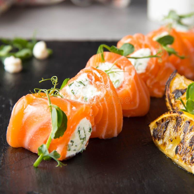 Rotoli di color salmone farciti con formaggio cremoso e le erbe, bello spuntino, alimento elegante per il menu immagini stock libere da diritti