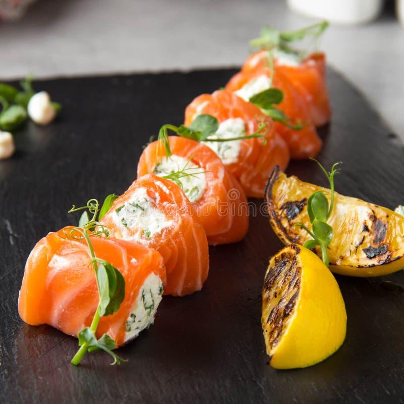 Rotoli di color salmone farciti con formaggio cremoso e le erbe, bello spuntino, alimento elegante per il menu fotografie stock