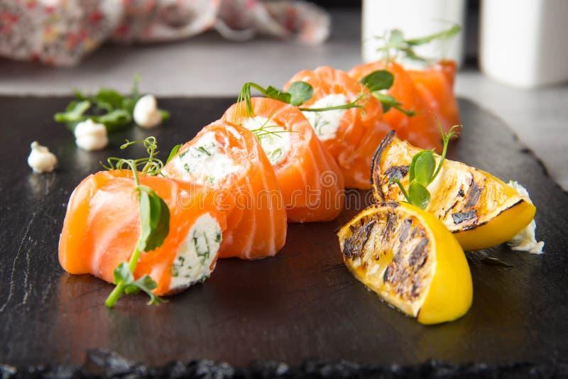 Rotoli di color salmone farciti con formaggio cremoso e le erbe, bello spuntino, alimento elegante per il menu immagini stock
