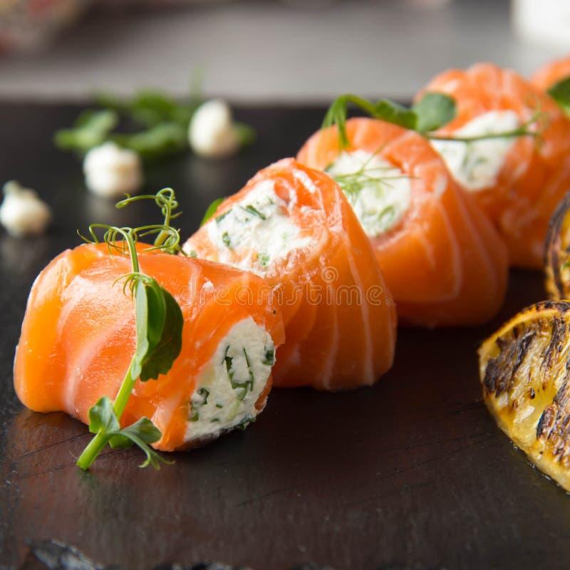 Rotoli di color salmone farciti con formaggio cremoso e le erbe, bello spuntino, alimento elegante per il menu immagine stock
