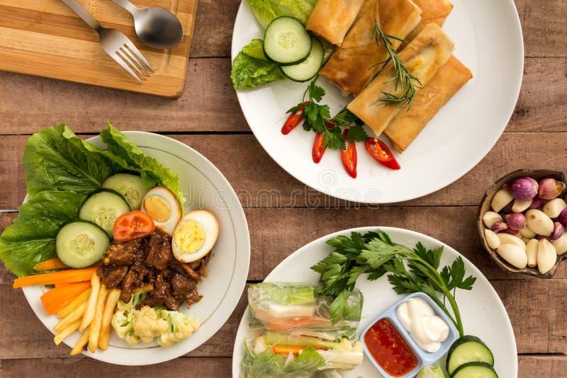 Rotoli di molla asiatici di stile con le verdure miste ed il manzo satay sulla tavola fotografia stock